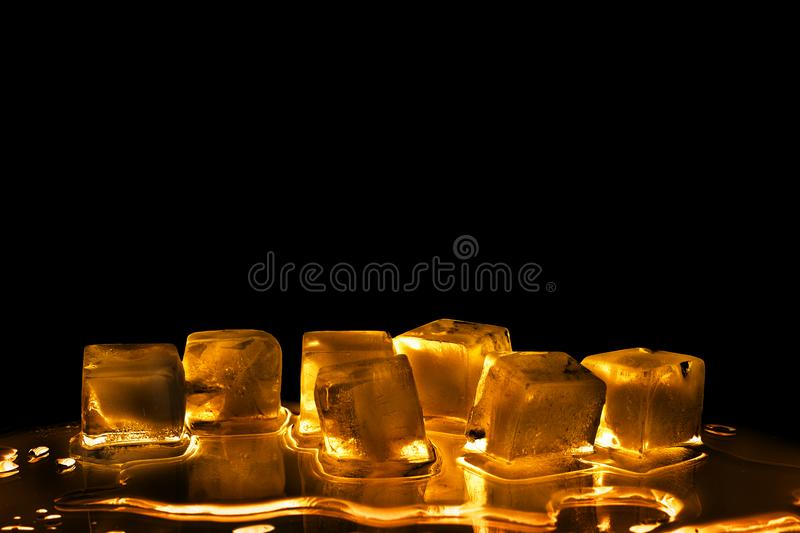 Golden ice cubes on black background isolated closeup, transparent frozen melting amber color water, yellow back light, reflection stock photo