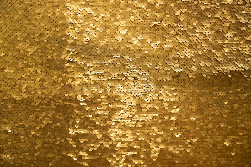 Golden and iridescent sequins texture background stock image