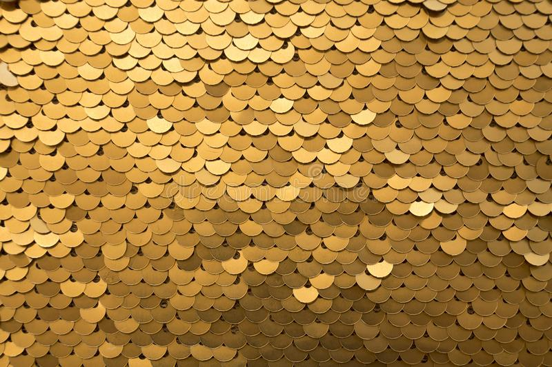 Golden and iridescent sequins texture background royalty free stock image
