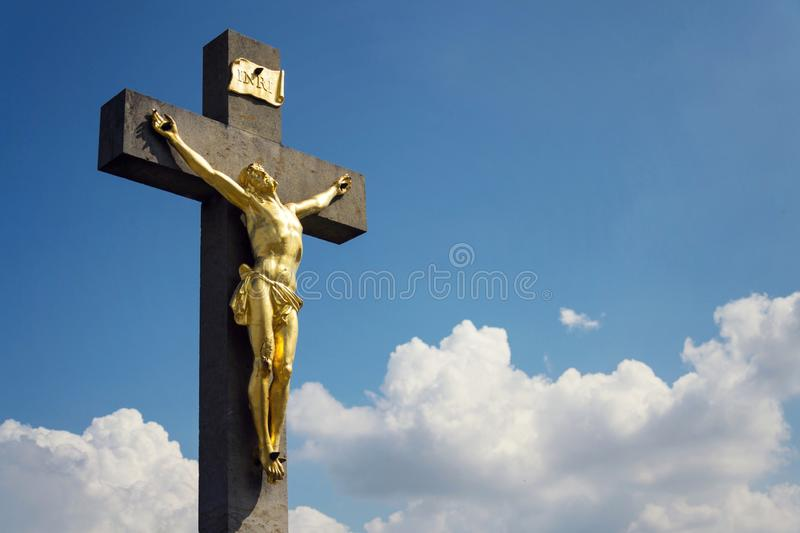 Golden Jesus Christ crucifixion statue, sunny summer day blue sky background stock photos