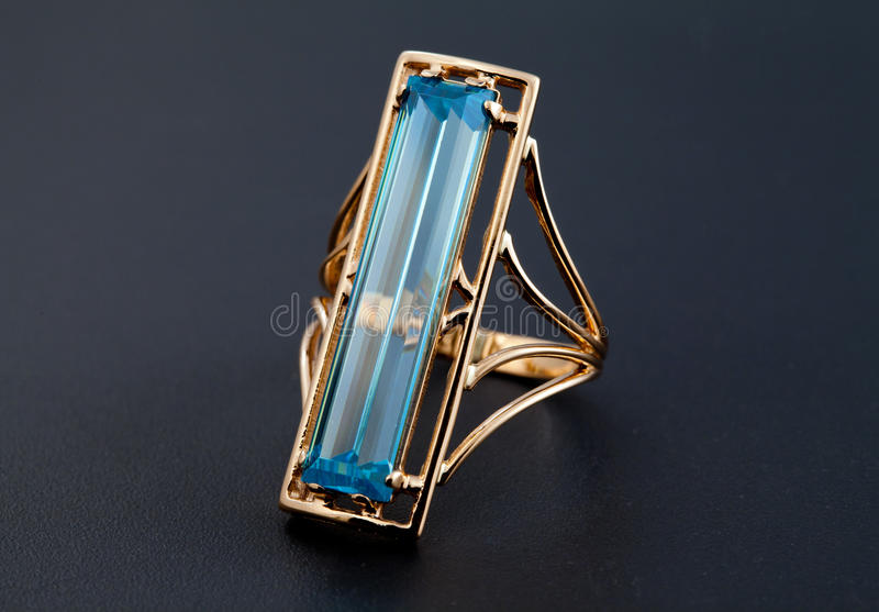 Golden jewelry ring with blue topaz royalty free stock photos