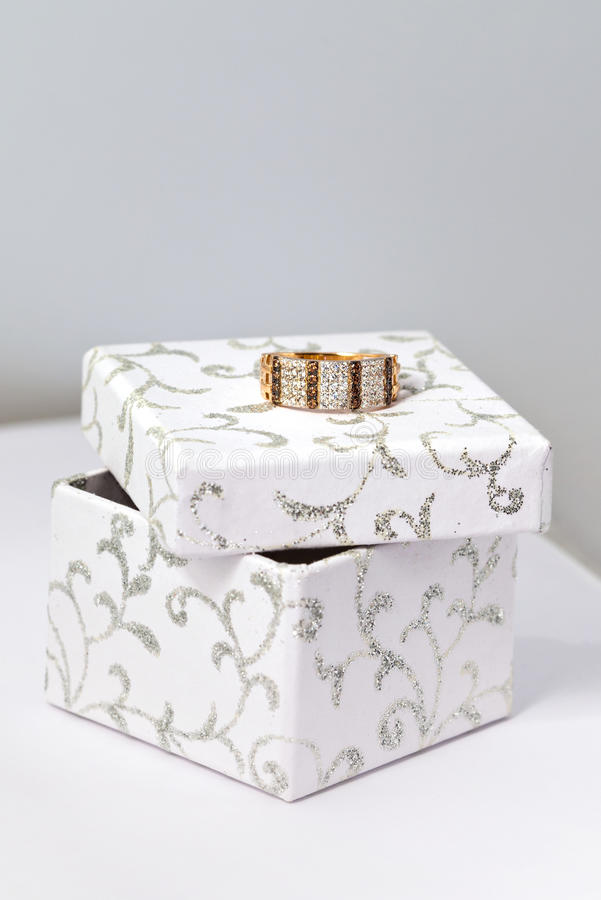 Golden ring on white box stock photography