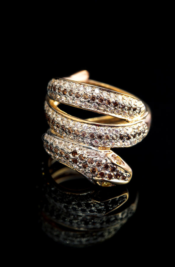Golden jewelry ring - serpent. Golden jewelry accessories - ring serpent with brilliants on black background royalty free stock photography