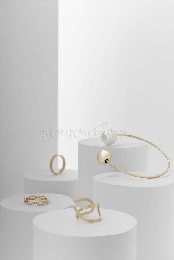 Golden jewelry, bracelet and different golden rings on white background. Golden jewelry, bracelet and different golden rings on white cylinder background royalty free stock photos