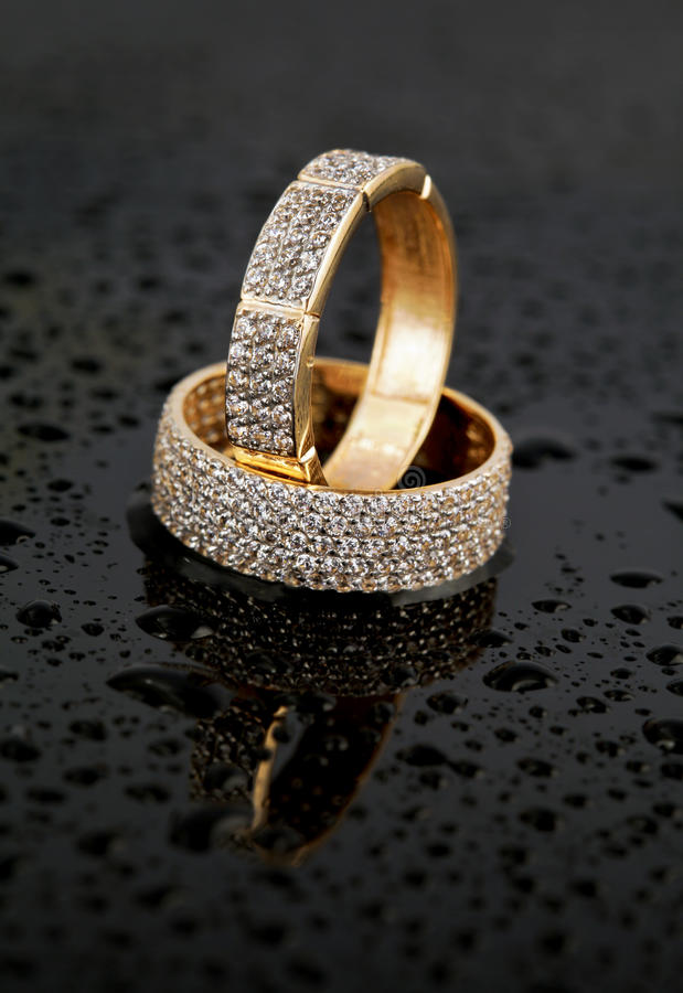 Golden jewelry two rings. With brilliants on black glass background with water drops stock image