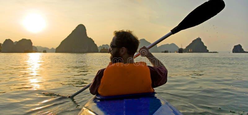 Golden Kayaking. A kayaker paddles among the golden sunlit monoliths of Halong Bay in Vietnam royalty free stock image