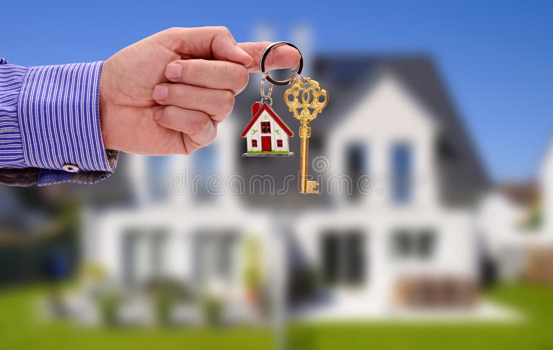 Golden key in hand of real estate manager stock image