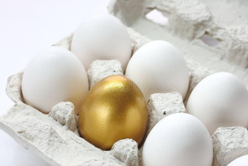 Golden kippeneieren en witte eieren in een doosje op een wit stock afbeelding