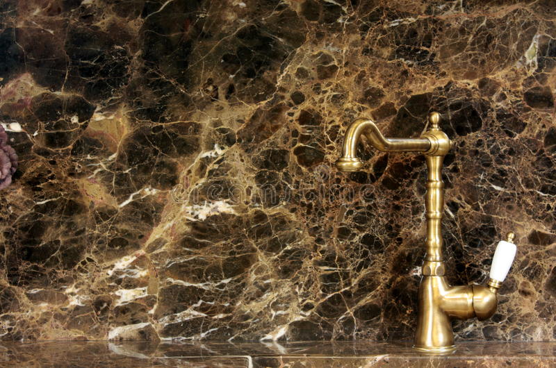 Golden kitchen tap. In a classic kitchen with marble worktop and wall panel stock photos