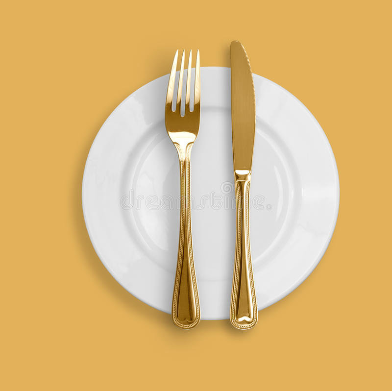 Golden Knife, fork and plate on beige background. Knife, plate and fork on yellow background royalty free stock image