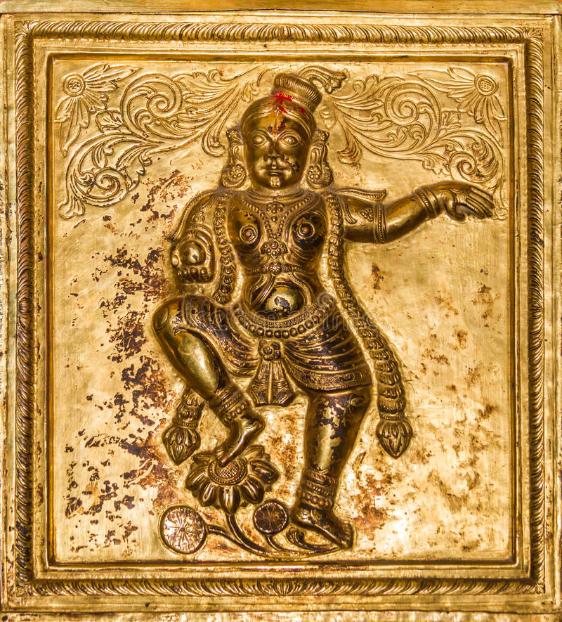 Golden Krishna. A gold embossed image of the Hindu god Krishna holding a laddu on the column of the hill temple Melkote in South India royalty free stock images