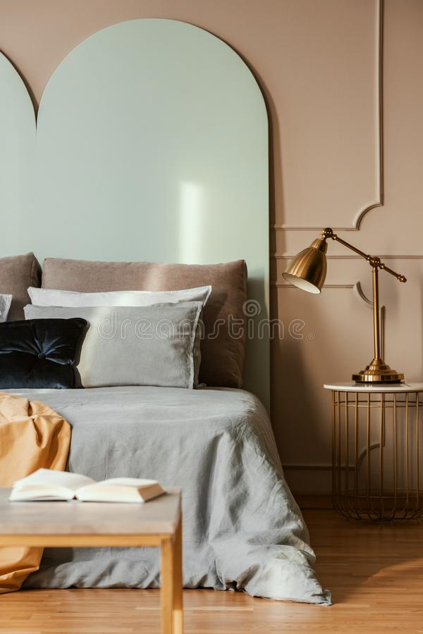 Golden lamp on modern nightstand table next to blue bed in grey bedroom interior. Golden lamp on modern nightstand table next to blue bed in interior royalty free stock image
