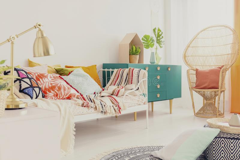 Golden lamp on nightstand in boho girl`s bedroom with colorful bedding on bed, green wooden cabinet and peacock chair with pillow. Concept royalty free stock image