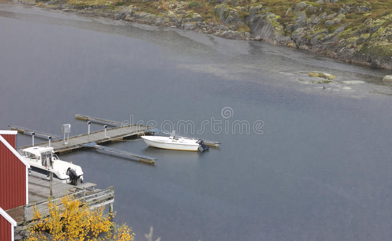 Golden Landing Stage. Autumn by the seaside in northern Norway. A landing stage with two sporty boats seeming ready for a nice tour though clear blue water stock image