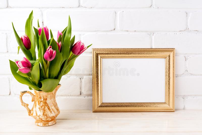 Golden landscape frame mockup with pink tulips in jug. Golden landscape frame mockup with bright pink tulips bouquet in gold jug near white painted brick wall royalty free stock photo