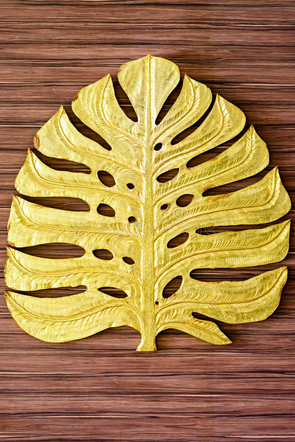 Golden leaf sculpture with wooden background. royalty free stock photography