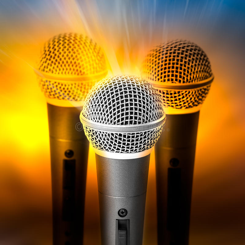 Golden light on microphone. Golden light on triple silver microphone on blured background stock images