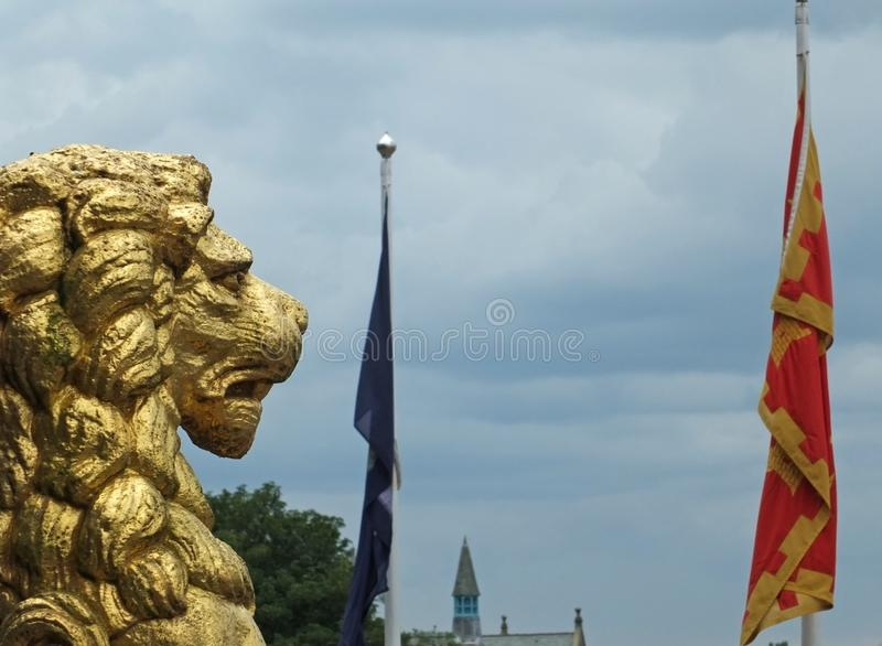 Golden lion statues in profile decorating the historic rochdale town hall against a dramatic sky with town flag in the distance. The golden lion statues in royalty free stock photo