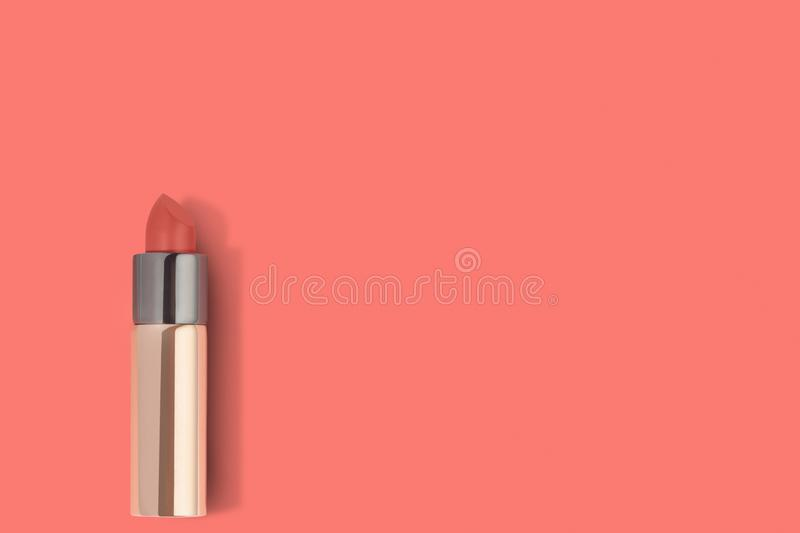 Golden lipstick on coral color background and copy space. Golden lipstick on coral color paper background with copy space stock images