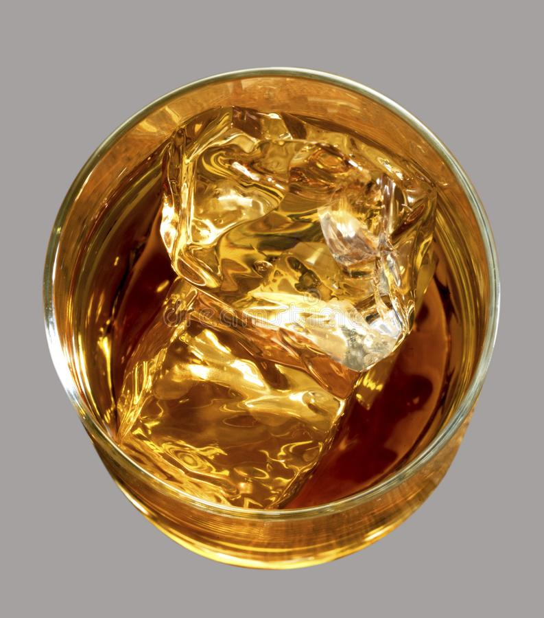 LIQUOR ROUND GLASS FROM ABOVE WITH ICE CUBES. Golden liquor drink in round glass shot from above with clear ice cubes in liquid stock photos