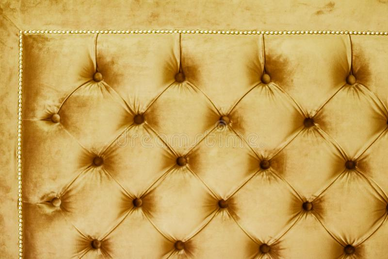 Golden luxury velour quilted sofa upholstery with buttons, elegant home decor texture and background stock photos