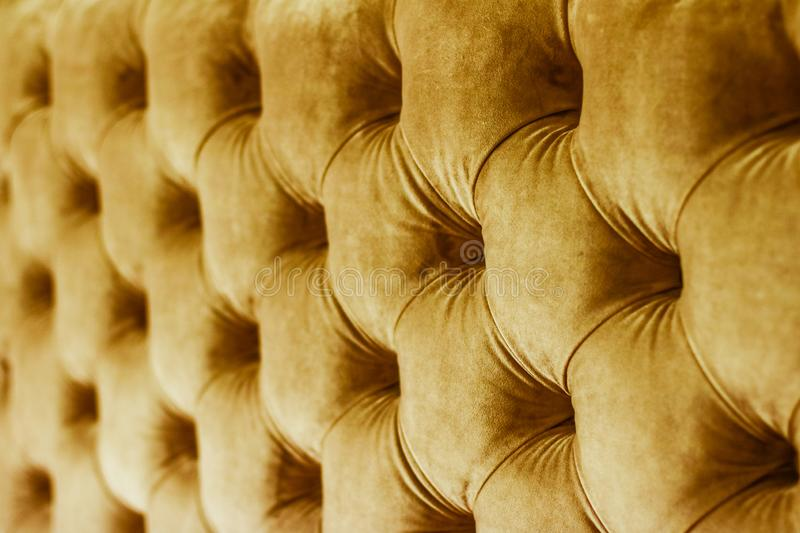 Golden luxury velour quilted sofa upholstery with buttons, elegant home decor texture and background. Furniture design, classic interior and royal vintage royalty free stock image