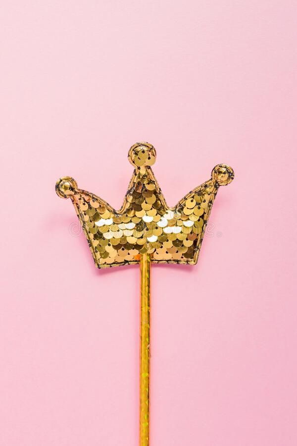 Golden magic stick from sequins in crown shape on pastel pink backgeound. Creative flat lay in minimal style.  royalty free stock photography