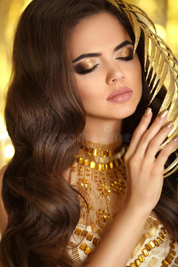 Golden makeup. Elegant brunette woman. Fashion jewelry. Wavy hair style. Matte lips. lady model in golden dress with gold ac. Cessories over bokeh lights party stock photos