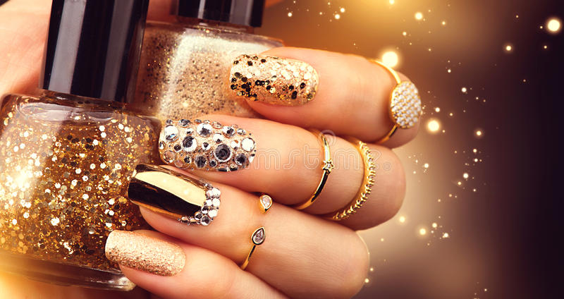 Golden manicure with gems and sparkles. Bottle of nailpolish, trendy accessories stock images
