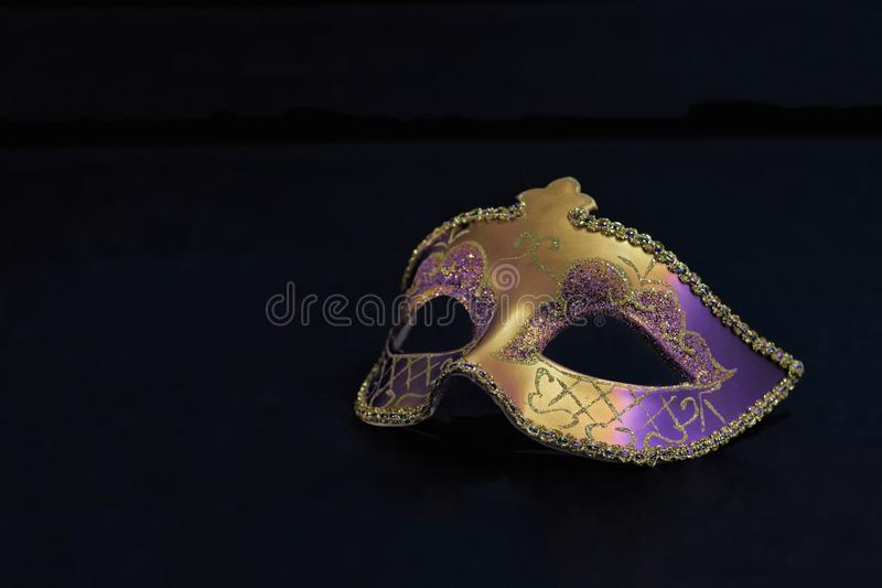 Golden Mardi Gras or Carnival mask isolated on a black background. stock photos