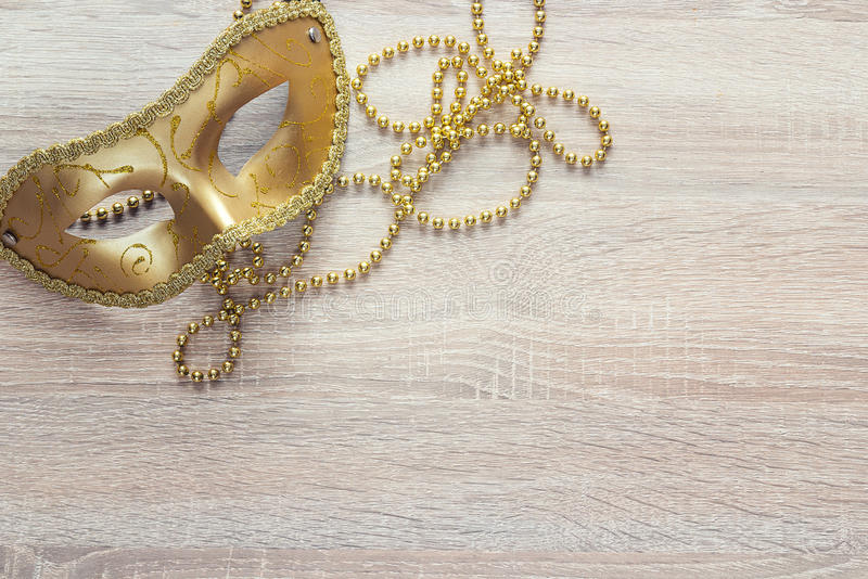 Golden Mardi Gras masks and beads on a wooden background. Copy space for text stock image
