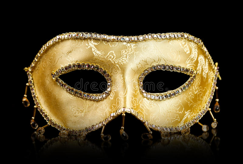 Golden mask on black. Golden decorated carnival mask with reflections on black royalty free stock photos