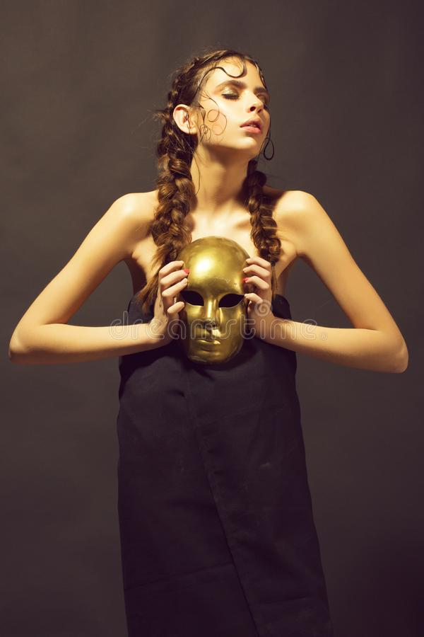 Golden mask in hand of mysterious beautiful woman, glamour stock photo