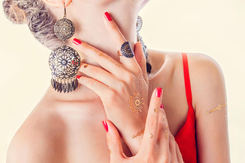 Golden mehendi tattoo on woman& x27;s hands with red manicure royalty free stock photos