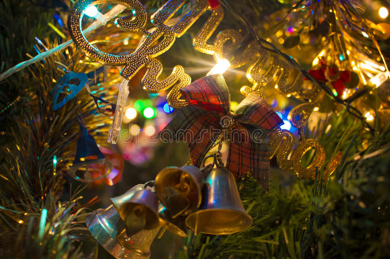 Golden Merry Christmas words on a branch of New Year tree. Lightened Golden Merry Christmas words on a branch of New Year tree royalty free stock images