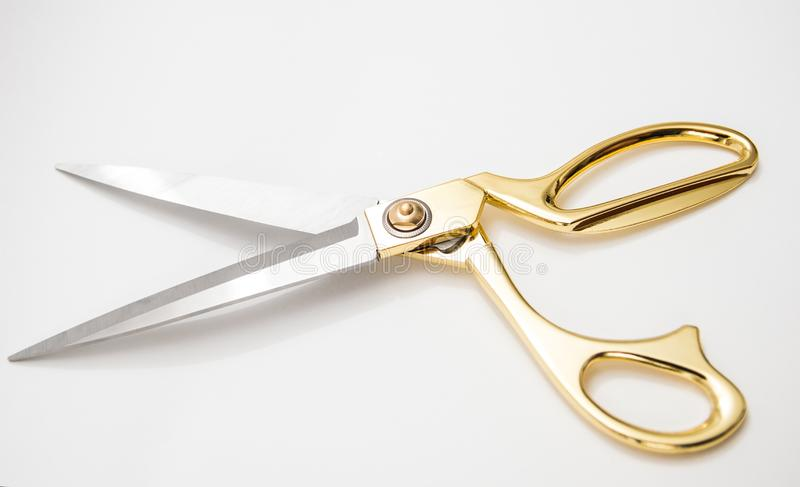 Golden metal scissors for cutting lie on a white background stock photos