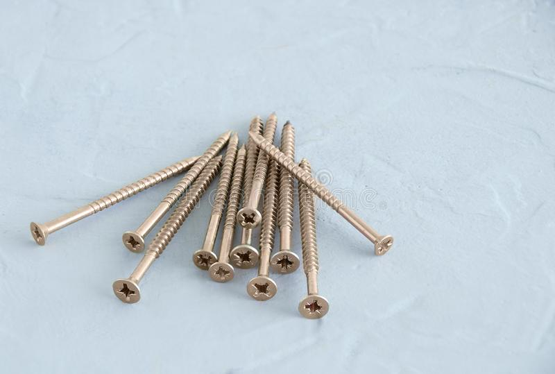 Golden metal screws for walls. On a gray concrete background royalty free stock image