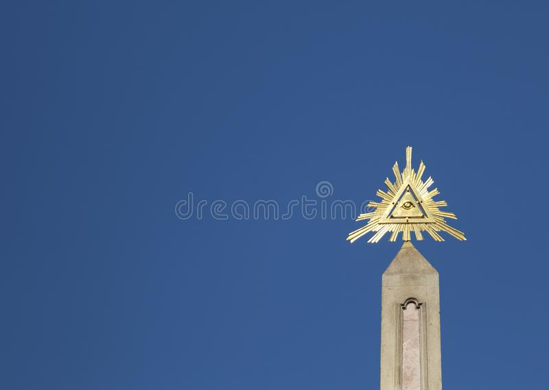 Golden Metal Symbol of Eye of Providence. On blue background stock image