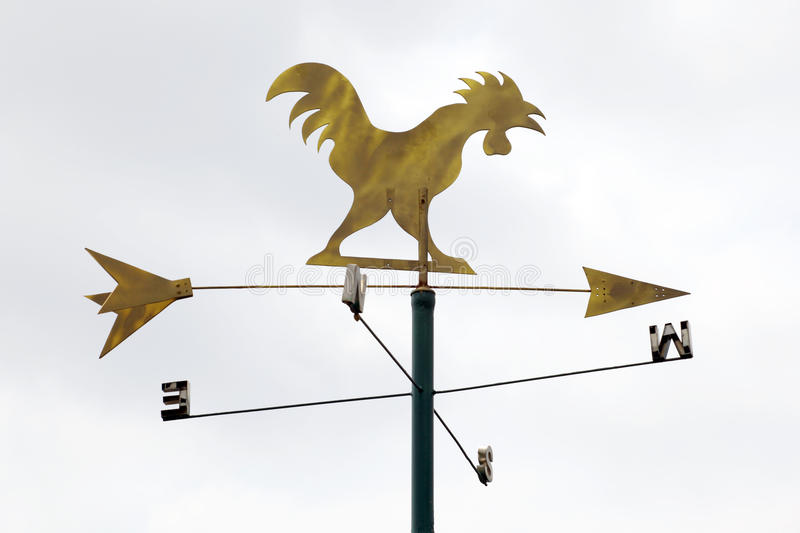 Golden metal weathervane over the white sky background. royalty free stock images