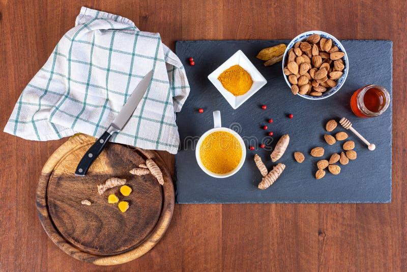 Golden milk, en traditionell indisk dryck som har sina rötter i Ayurveda Ingredienserna är gurkpulver, mandelmjölk och honung arkivbild
