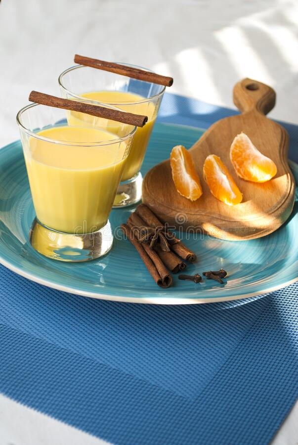 Golden milk, spices, cinnamon. Winter drink. Blue background. Sun shadow.  Slices of mandarin royalty free stock image