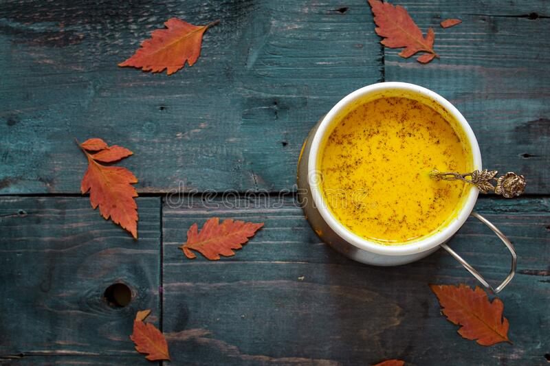 Golden milk in a white cup. Wooden color blue background. Autumn leaves. A healthy drink made from milk, turmeric, cinnamon and. Honey. Yellow milk royalty free stock images