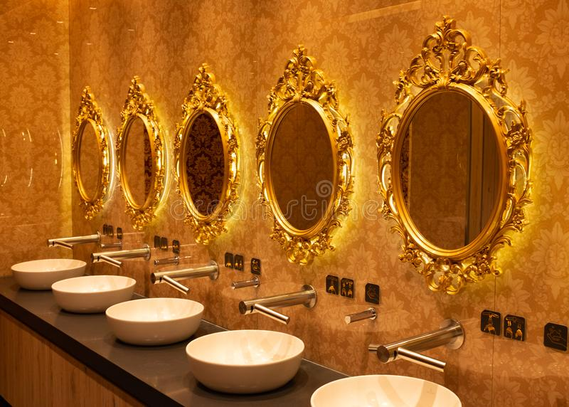Golden mirrors above washbasins in the bathroom. View of the golden mirrors above washbasins in the bathroom stock images