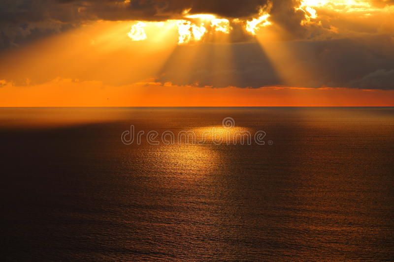 Golden morning at calm sea. Early morning atmosphere over the calm sea at the Gold Coast, Australia, with sun rays streaming through dark clouds, spotlighting