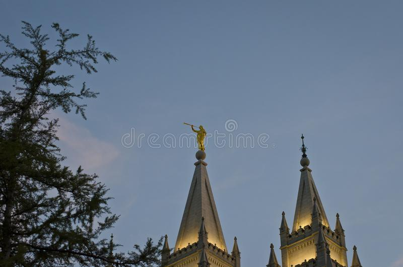 A golden moroni on the top of the salt lake mormon temple. A view of the golden moroni on the tops of he salt lake city temple in the park under the evening sun royalty free stock images