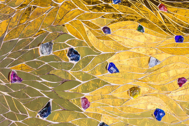 Golden mosaic decorated with colored stones background. Shiny yellow gold color decorative texture Bright brilliant glossy metalli stock photo