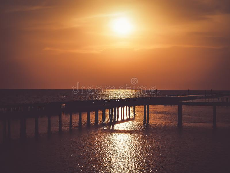 Golden natural sea sunset view of jetty or small bridge at horizon with silhouette and orange sky landscape. Sunset or sunrise stock photos