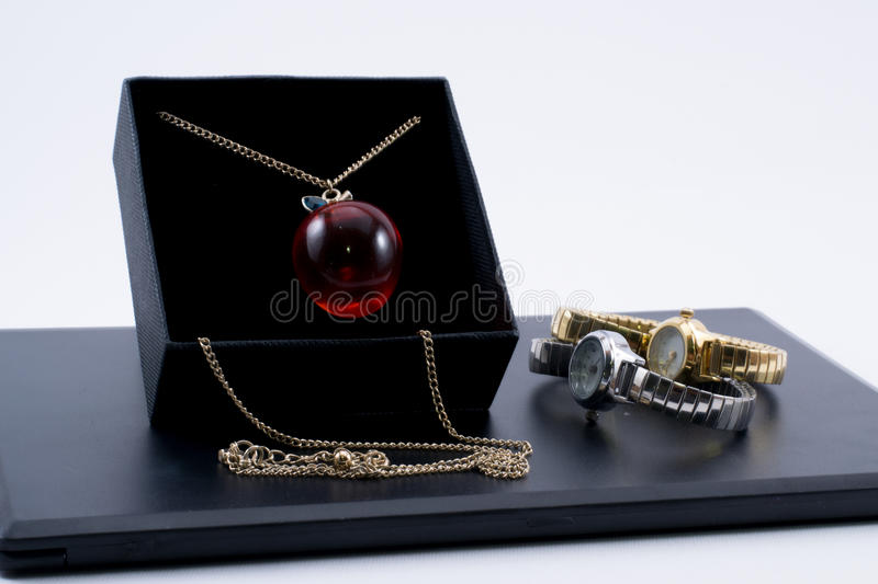 Golden necklace in a box and two beautiful watches royalty free stock image