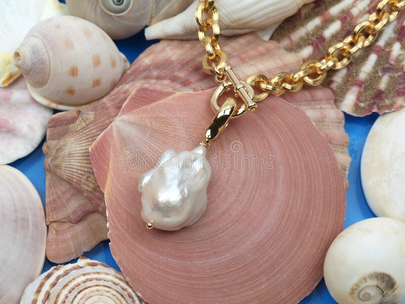 Golden necklace with white baroque pearl pendant stock image
