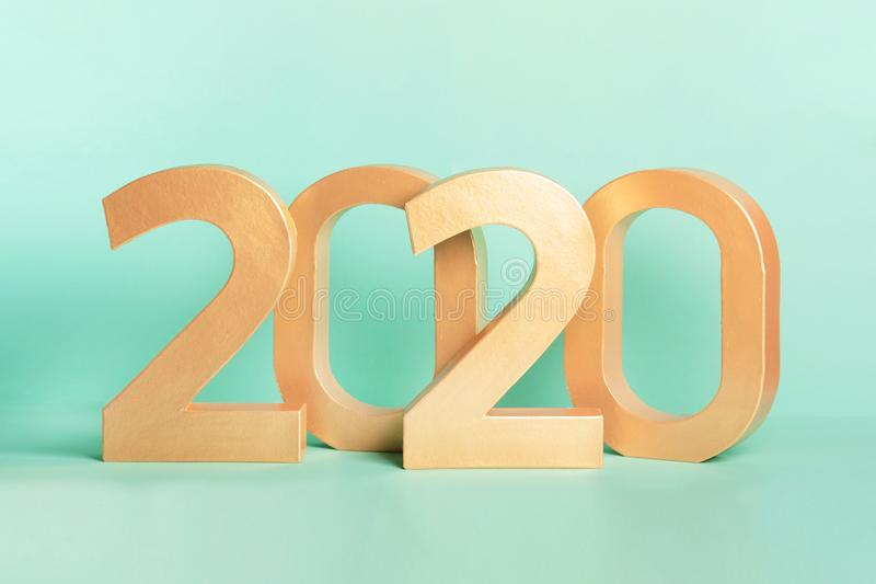 Golden new year 2020 number digits isolated on neon mint background. stock photos